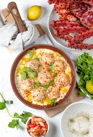 CRAB MEATBALLS crab meatballs in white creamy sauce in red pan, whole king crab, cilantro, lemon and white wine on white background. Banco de Imagens