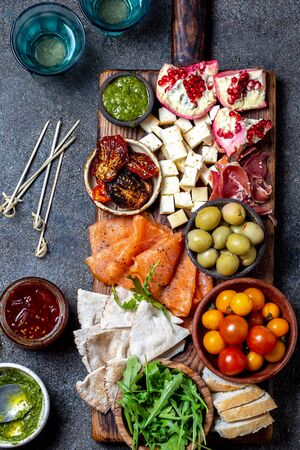 Antipasto. Wine set appetizer. Ham serrano, smoked salmon, dried and fresh tomatoes olive cheese, wine on board. Top view, gray concrete background.