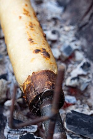 Preparation of food at Chiloe island, Chile. Chiilotan potato bread prepared on wooden stick.