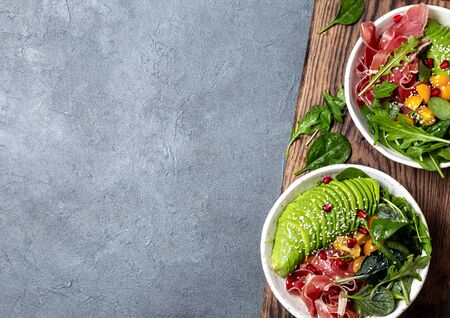 carbs bowl. Fresh salad with green spinach, rucola, avocado and ham serrano in white bowl, gray background, top view.