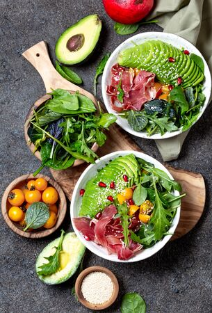 Low carbs bowl. Fresh salad with green spinach, rucola, avocado and ham serrano in white bowl, gray background, top view.