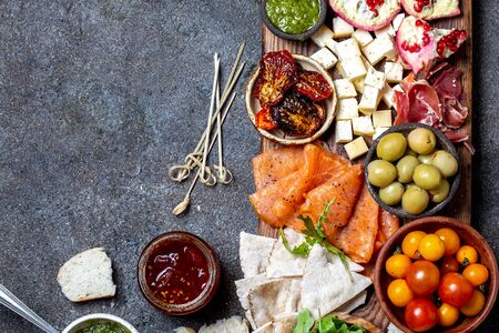 Antipasto. Wine set appetizer. Ham serrano, smoked salmon, dried and fresh tomatoes olive cheese, wine on board. Top view, gray cncrete background. 写真素材