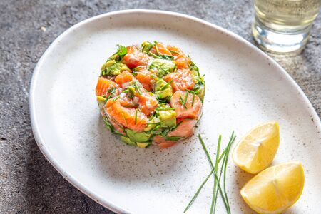 PERUVIAN FOOD. Salmon ceviche with avocado, spring onion and lemon on white plate served with white wine. Stockfoto