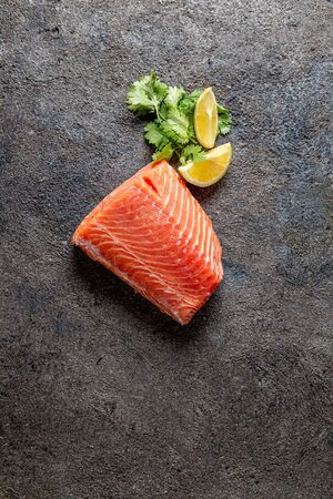 Food background with fresh salmon filet steak, lemon and coriander.