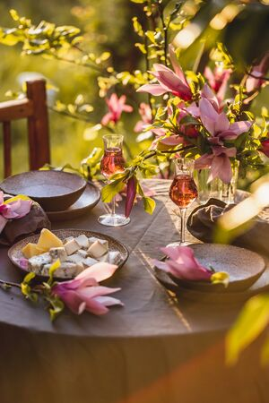 Table Setting in Garden on Sunset Light. Table decorated with magnolia flowers under magnolia tree. Foto de archivo - 130165763