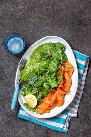 Low carbs salad. Spinach, rucola salad with avocado and salmon. Black concrete background, white plate, top view
