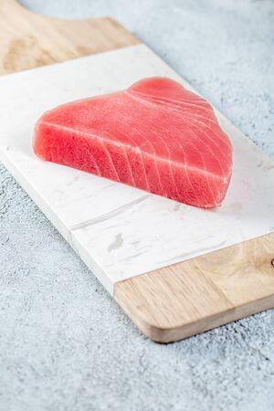 Raw tuna steak on white concrete background. Stock fotó