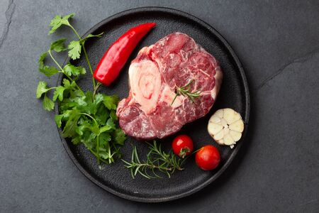 Raw fresh ossobuco con herbs, garlic and chile pepper on black plate. Dark background. Stock fotó