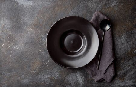 Food background with black empty plate, gray napkin and black spoon on dark background.