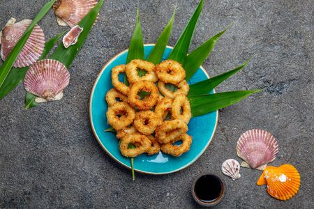 Fried squids rings on blue plate decorated with tropical leaves. Gray concrete background and sea decoration. Top view Stock fotó
