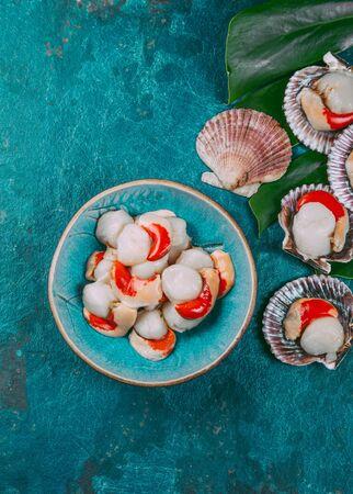 Capesante crude dei crostacei dei frutti di mare freschi su fondo blu.