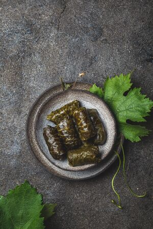 Traditional Middle Eastern dolma or tolma. Grape leaves stuffed with meat and rice. On Gray plate, gray concrete background. Archivio Fotografico - 130165471