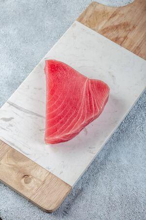 Raw tuna steak on white concrete background