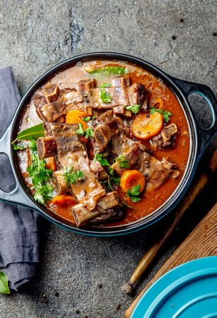 Bourguignon beef ribs stewed with onion, carrot in red wine Фото со стока