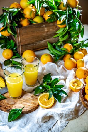 Table with box of fresh orange with orange tree branch and fresh orange juice. Stock fotó