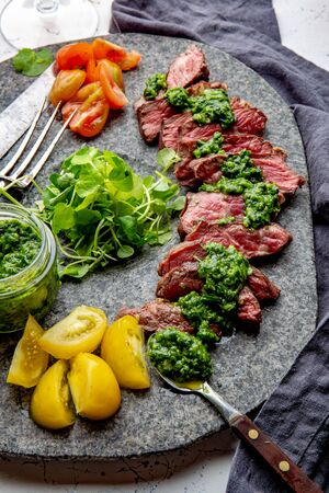 Slices of beef steak with chimmichuri sauce on gray stone plate.