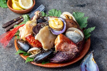 Famous traditional dish of the south of Chile and the Chiloe archipelago - Curanto Kuranto.  Different seafood and meat cooked in a pit on the coals under the ground. Фото со стока