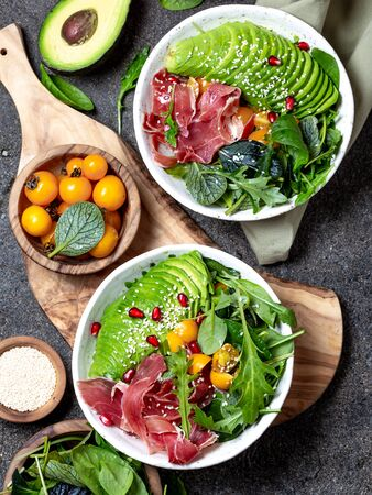 Low carbs bowl. Fresh salad with green spinach, rucola, avocado an ham serrano in white bowl, gray background, top view. Stock fotó