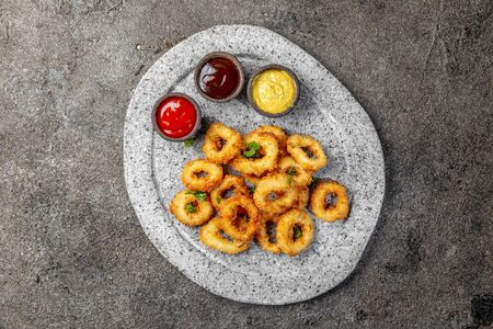 Fried squids rings on gray stone plate with sauces. Gray concrete background. Stock fotó