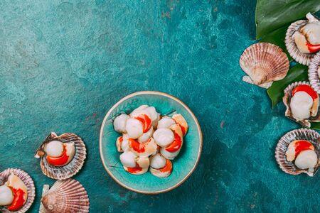 Raw fresh seafood shellfish scallops on blue background. Zdjęcie Seryjne