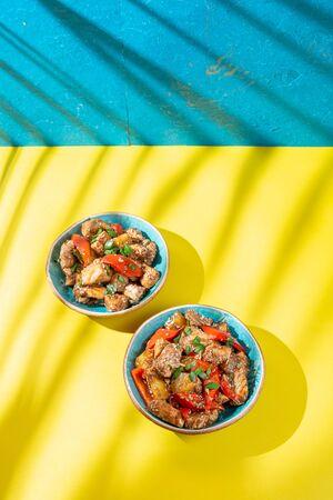 Hawaiian pinapple chicken in blue bowls on yellow blue background. Trendy sunlight effect. Zdjęcie Seryjne