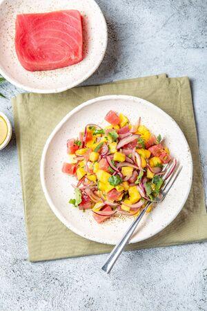 Gourmet tuna mango salad tartar with cilantro and purple onion on white plate.