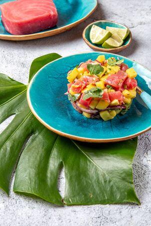 Tropical style gourmet tuna mango salad tartar with cilantro and purple onion. On blue plate, tropical leaves. Zdjęcie Seryjne