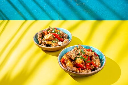 Hawaiian pinapple chicken in blue bowls on yellow blue background. Trendy sunlight effect. Stock fotó