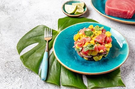 Tropical style gourmet tuna mango salad tartar with cilantro and purple onion. On blue plate, tropical leaves. Stock Photo