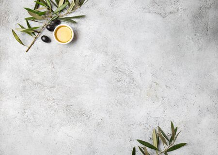 Food background with linen napkin, olive tree branch, olive oil on concrete background.