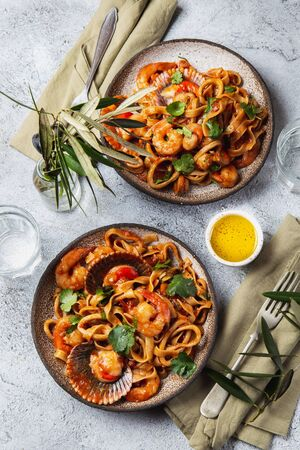 Seafood Spaghetti with seashells, prawns, squids on gray background. Italian mediterranean food concept.