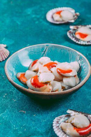Rohe frische Meeresfrüchte Muscheln Jakobsmuscheln auf blauem Hintergrund.