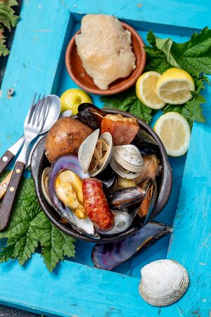 Famous traditional dish of the south of Chile and the Chiloe archipelago - Curanto Kuranto.  Different seafood and meat cooked in a pit on the coals under the ground. Stock Photo