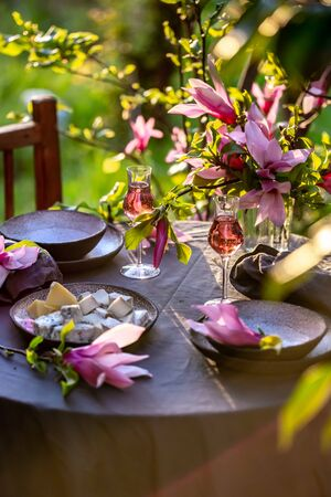 Beautiful table setting in garden on sunset light. Table decorated with magnolia flowers under magnolia tree