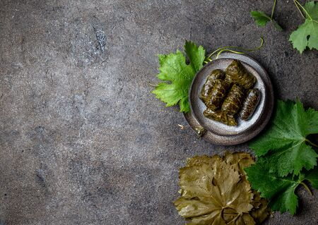 Traditional Middle Eastern dolma or tolma. Grape leaves stuffed with meat and rice. On Gray plate, gray concrete background. Stock Photo