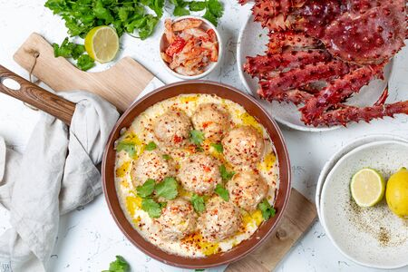 CRABMEATBALLS crab meatballs in white creamy sauce in red pan, whole king crab, cilantro, lemon and white wine on white background.