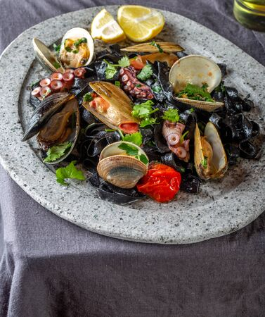 Seafood black fettuccine fehttuchini. Black pasta with squids, octopus clams, mussels on stone plate. Gourmet dish.