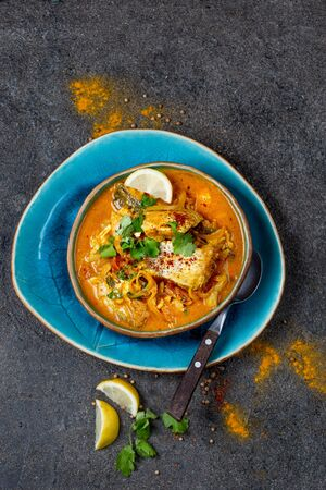 INDIAN FOOD. Traditional KERALA FISH CURRY with naan bread, gray plate, black background. Stock Photo