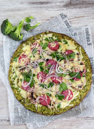 Crust Broccoli base low carbs keto pizza with salami, avocado on vintage newspapper. Top view.
