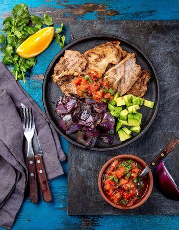Yucatan cibo messicano maiale POC CHUC poc chuck. Maiale marinato in succo d'arancia servito con avocado, cipolla viola e salsa rustica di pomodoro