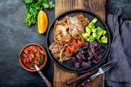 Yucatan cibo messicano maiale POC CHUC poc chuck. Maiale marinato in succo d'arancia servito con avocado, cipolla viola e salsa rustica di pomodoro Archivio Fotografico