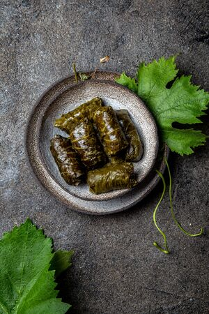 Traditional Middle Eastern dolma or tolma. Grape leaves stuffed with meat and rice. On Gray plate, gray concrete background. Stok Fotoğraf
