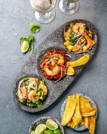 Coloresd ceviches with mango, avocado and tomatoes. White wine, lime and banana chips