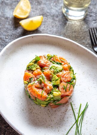 PERUVIAN FOOD. Salmon ceviche with avocado, spring onion and lemon on white plate served with white wine. Stok Fotoğraf