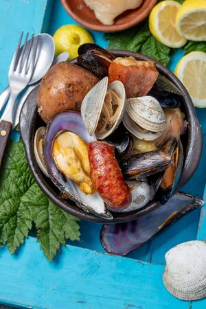 Famous traditional dish of the south of Chile and the Chiloe archipelago - Curanto Kuranto.  Different seafood and meat cooked in a pit on the coals under the ground. Stok Fotoğraf