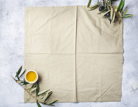 Food background with linen napkin, olive tree branch, olive oil on concrete background. Standard-Bild - 133654743
