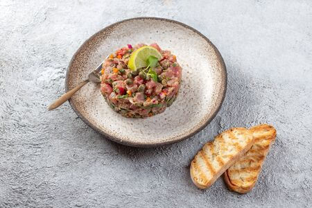 Tuna fish TARTAR tartare on gray plate.