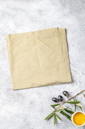 Food background with linen napkin, olive tree branch, olive oil on concrete background. Standard-Bild - 133654972