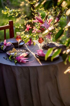 Beautiful table setting in garden on sunset light. Table decorated with magnolia flowers under magnolia tree.
