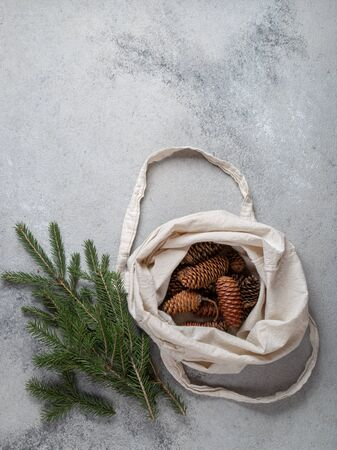 Zero waste Christmas concept. Natural Chirsmas decoration, pine cones and branches in linen bag. Flat lay, top view.